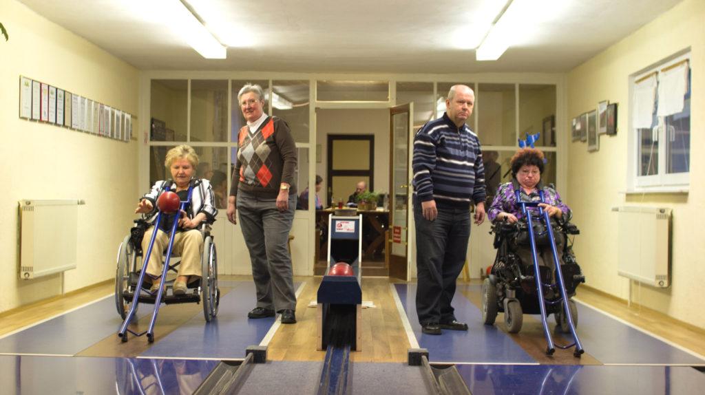 Zwei Rolli-Kegler treten auf zwei Bahnen gegeneinander an. Beide Kegler üben den Sport mit Hilfe der Kegelschiene aus.